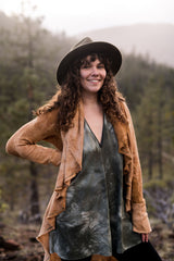 Woman wearing a brimmed heat with a cardigan and dress in front of forested mountains