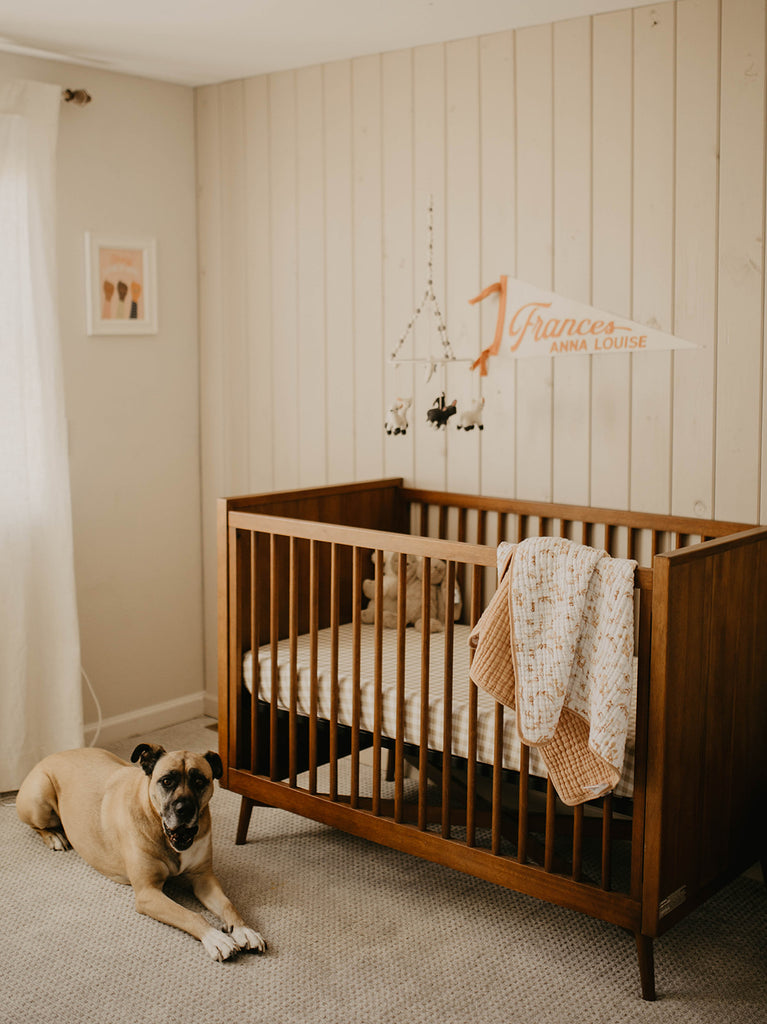 Far away view of crib with name banner on wall