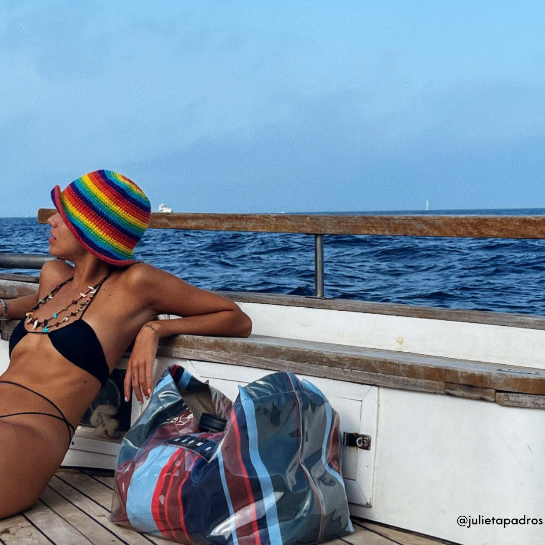 Model Julieta Padros posing for a photo while travelling on a boat wearing Sommer Swim's Nero Xena halter bikini top with accompanying bikini bottoms.