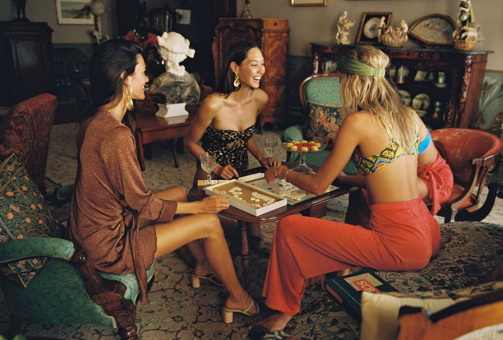 Group of models sitting in lounge room wearing cruise collection lounge pants, wrap dresses and wrap skirts