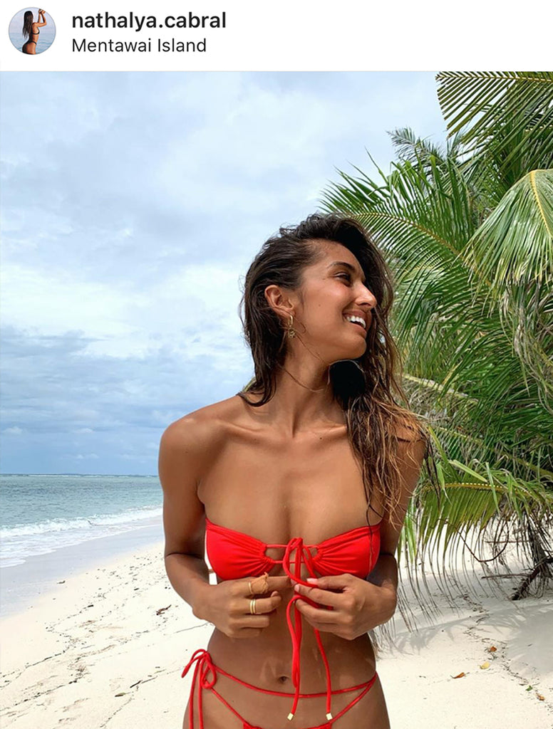 Influencer @nathalya.cabral wearing the Xena sommer swim bikini top has a tie-front bandeau at the beach