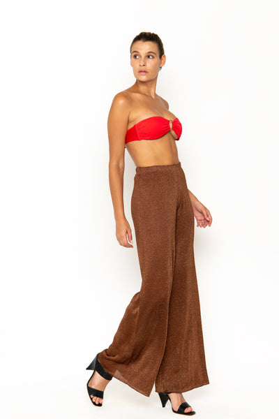 Sommer Swim model facing sideways to the left and wearing Calvi Lounge pant in Campari
