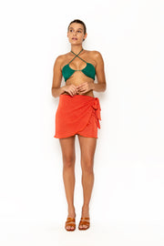 Sommer Swim model facing forward and wearing Salinas mini wrap skirt in Campari