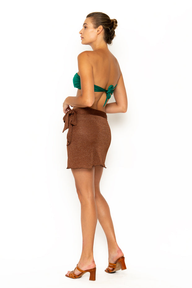 Sommer Swim model facing backwards and wearing Salinas mini wrap skirt in Cinnamon