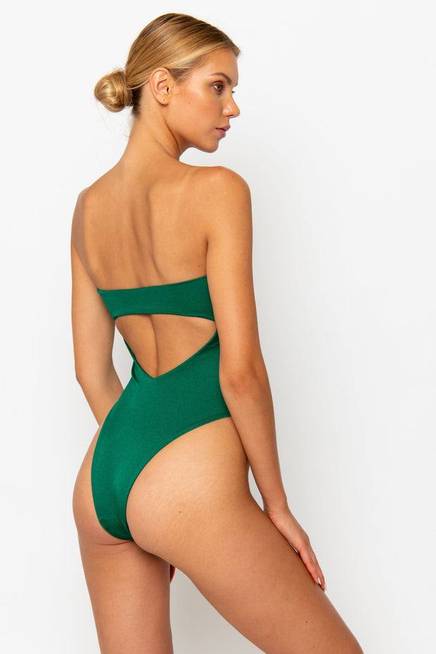 Sommer Swim model is facing backwards and wearing a high cut Maxim One-Piece swimsuit in Emerald