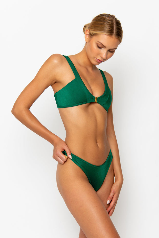 Sommer Swim model facing sideways to the left and wearing a Maya high leg bikini bottom in Emerald