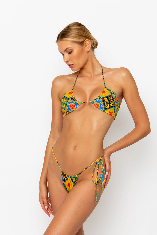 Sommer Swim model facing sideways to the right and wearing a Naomi tie side bikini bottom in Baroque