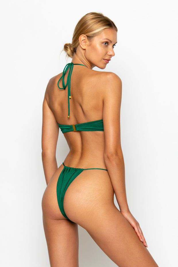 Sommer Swim model facing backwards and wearing a Naomi tie side bikini bottom in Emerald