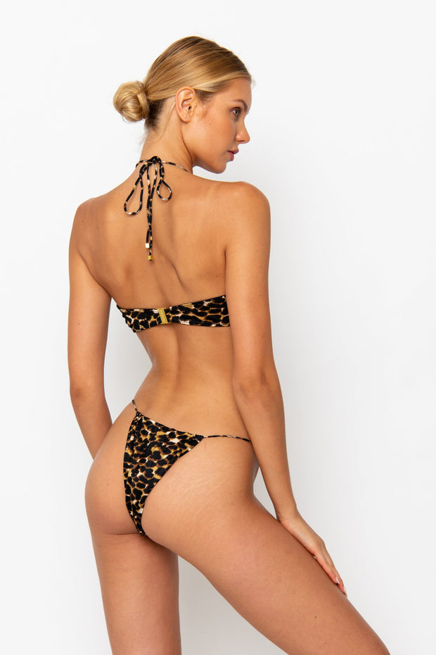 Sommer Swim model facing backwards and wearing a Xena halter stye bikini top in Leopard Luxe