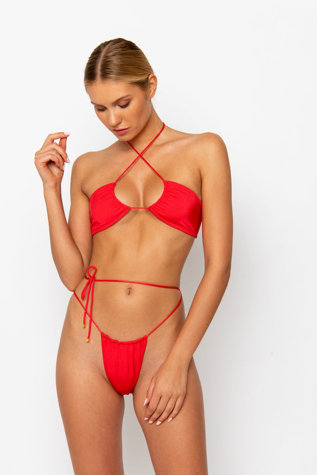 Sommer Swim Model facing sideways to the right and wearing a Xena halter style bikini top in Venere