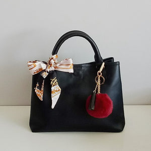 Curatelier Interlace Bag Handle Ribbon Scarf And Gloria Faux Fur Wine Red Pom Pom Keyring Bag Charm Featured on Velle Bella Rose Petite Tote Bag in Black