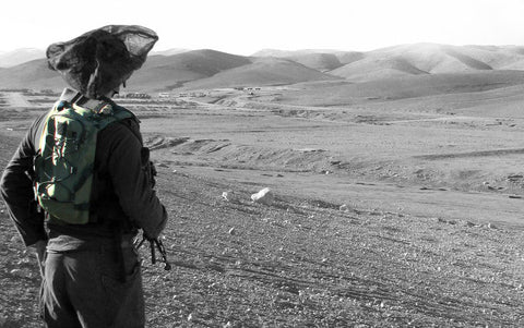 Soldier looking at view with bag