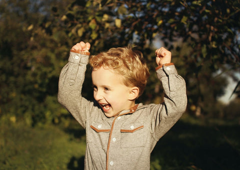 Excited child with hands in the air