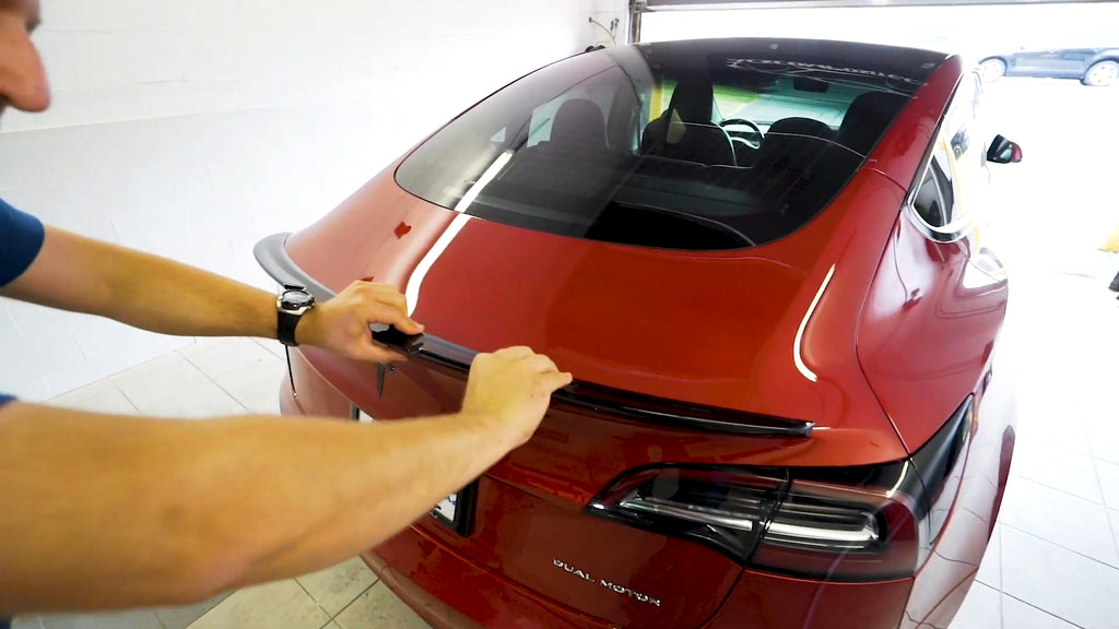 Apply final pressure to the spoiler to ensure a sealed installation.