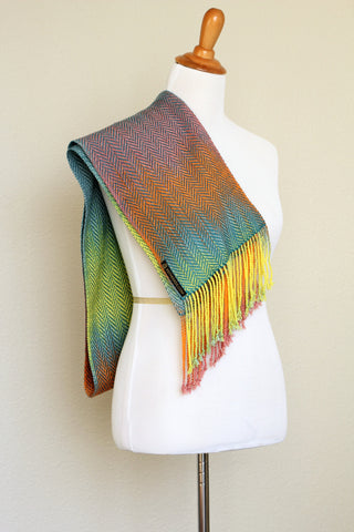 Woven scarf in blue, orange, purple and yellow colors with twill pattern and twisted fringe