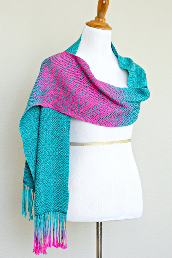Woven scarf in blue and neon pink with woven pattern and twisted fringe