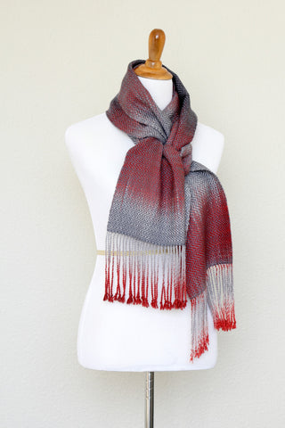 Woven scarf in red and grey colors with twill pattern and twisted fringe