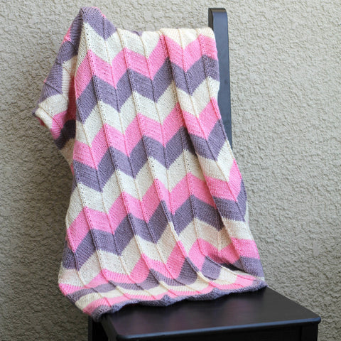 Pink knit baby blanket in chevron pattern