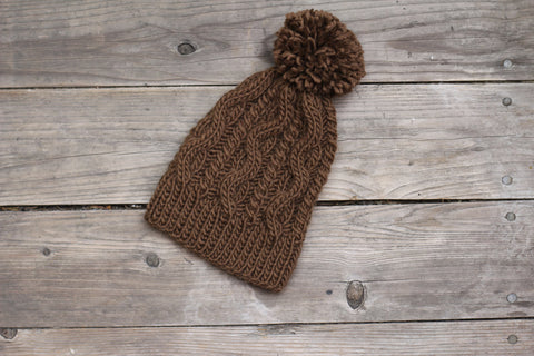 Knit brown hat with cables and pom pom