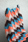 Knit baby blanket in orange and teal colors