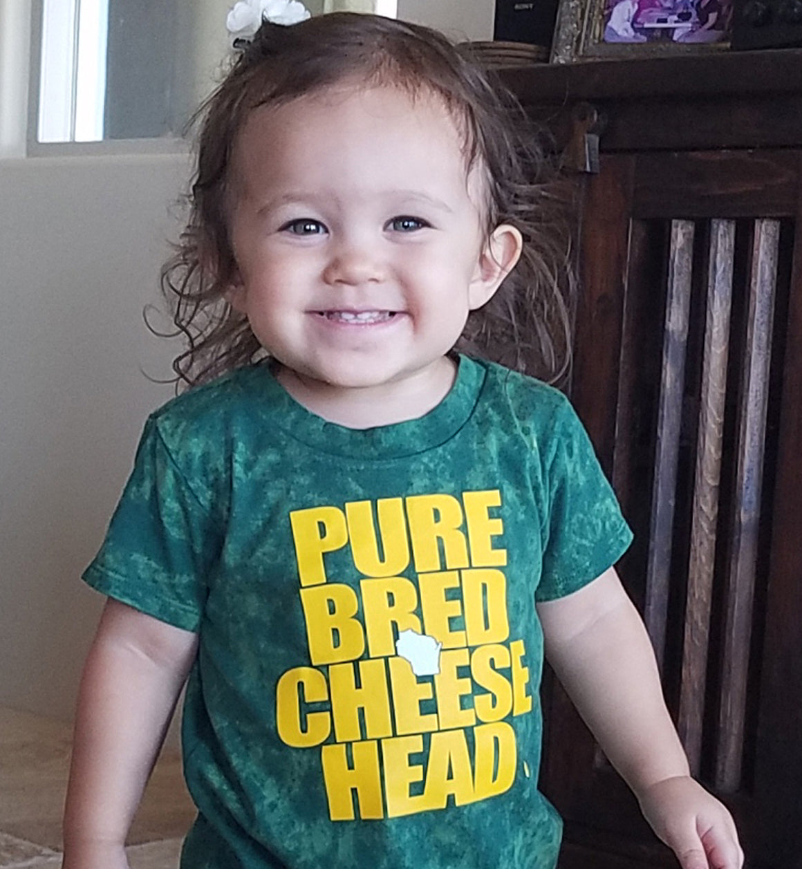 baby girl wearing a cheesehead shirt