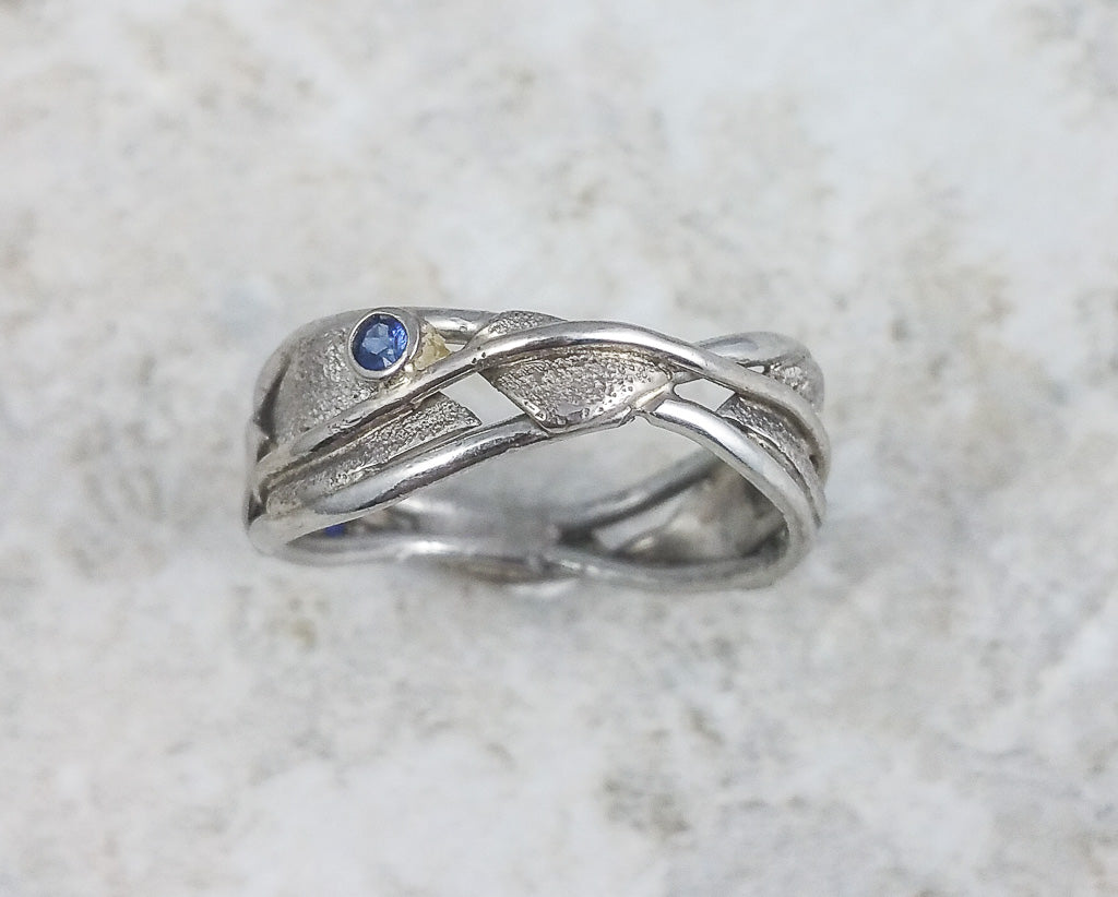 Leaf and vine wavy band in white gold with sapphire accent