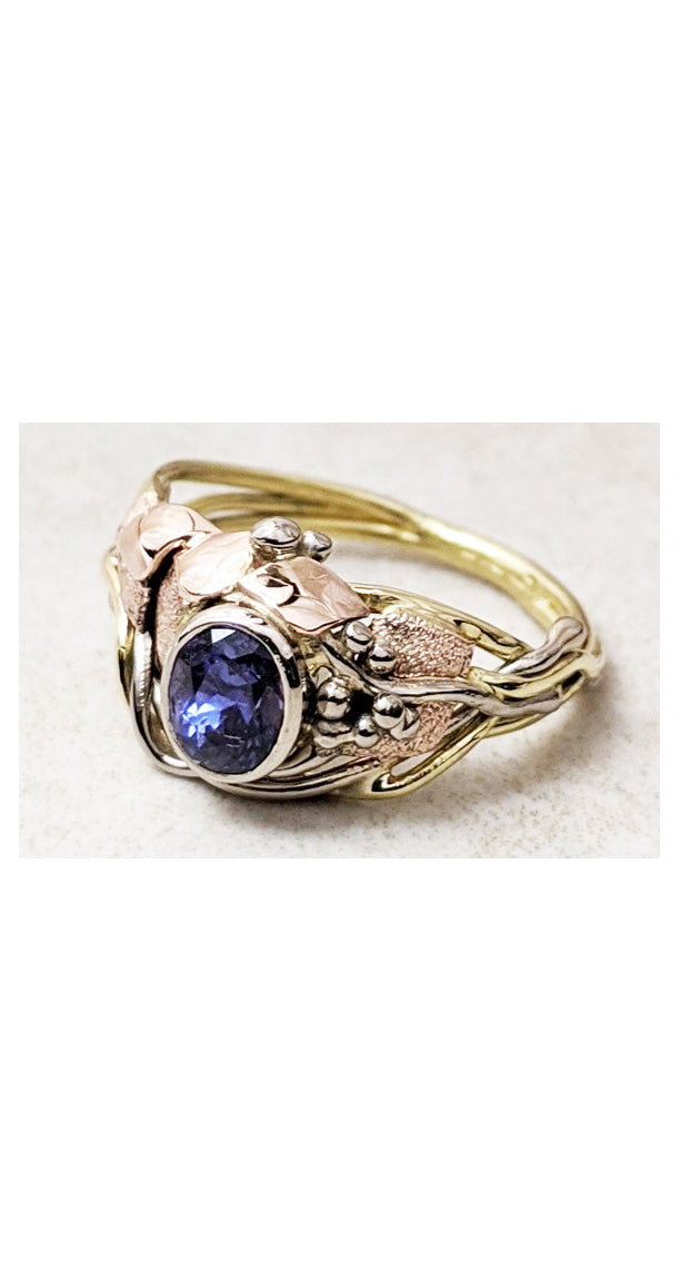 Asymmetrical design ring with bezel set purple sapphire