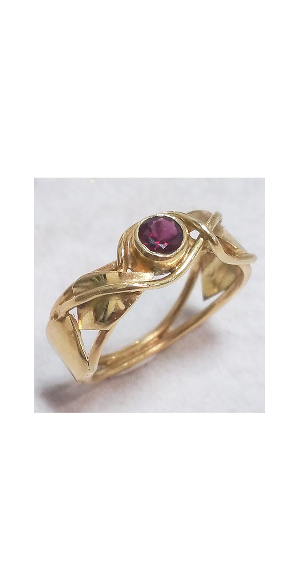 Band style ring with bezel set garnet