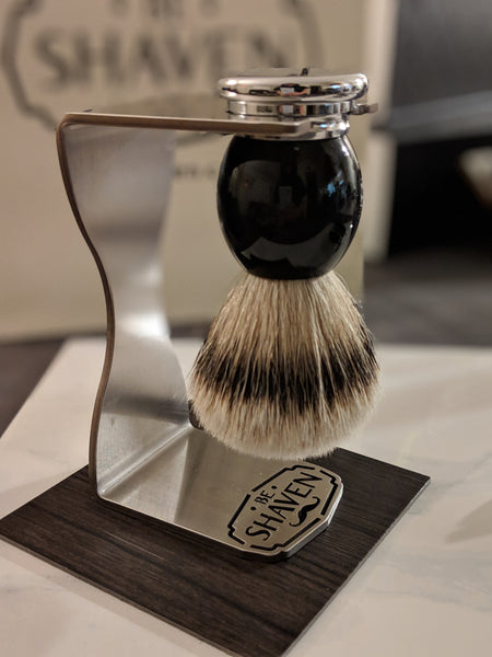 black chrome silvertip badger hair shaving brush hanging on stainless steel stand