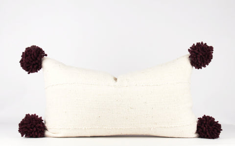 White mud cloth pillow with pom poms