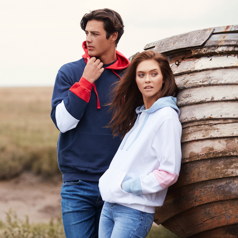 Guy and girl model both wearing bold, striped hoodies