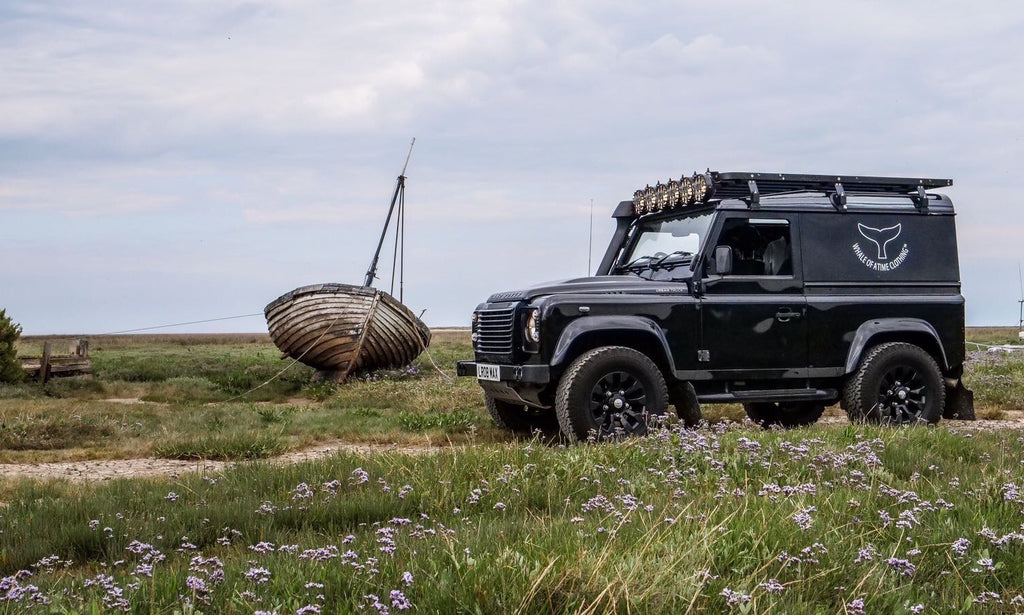 Black Land Rover Defender with the Whale Of A Time Clothing logo on the side, stationary on a marsh with an old wooden boat in the background.