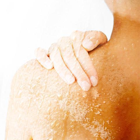Woman exfoliating with BFR body scrub