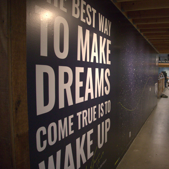 Common Thread Collective office wall reads: The best way to make dreams come true is to wake up
