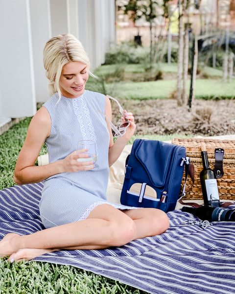 girl in blue in white dress sitting on a picnic blanket drinking wine