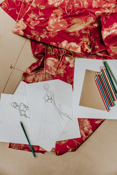 Fashion Illustration by David Peck with colored pencils and fabric draped on a cutting table