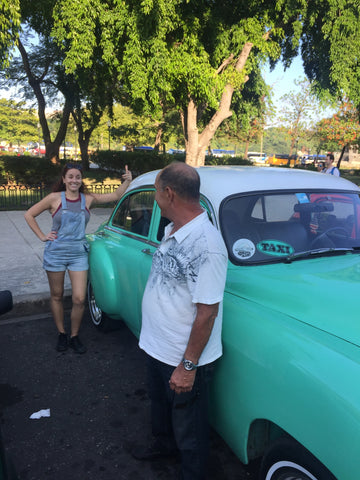 Jackie standing by a Cuban taxi.