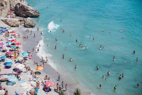 Beachgoers swimming in the ocean on a hot summer day.