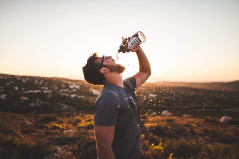 Man drinking water to stay hydrated in the summer.