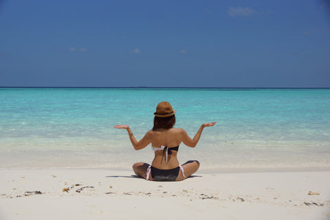 Woman sitting out on the beach in summer.