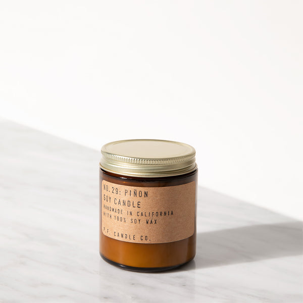 PF Candle Co Classic Line Pinon mini candle in an amber glass jar with kraft label and brass lid