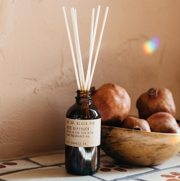 Black fig reed diffuser on a colorful tile counter in front of a bowl on pomegranates with a rainbow prism above