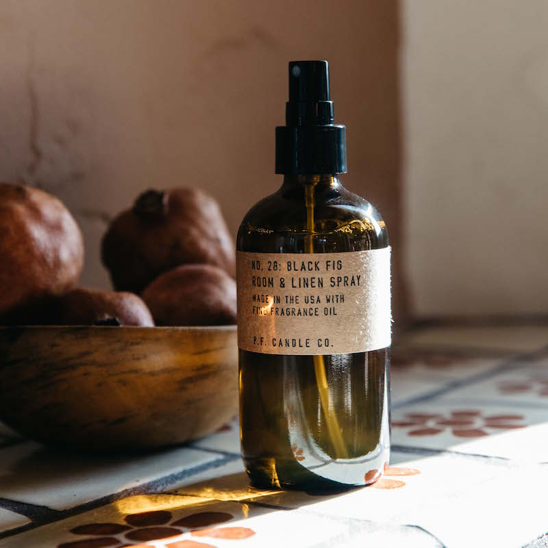 PF Candle Co Black Fig room & linen spray on a tile counter next to a bowl of pomegranates