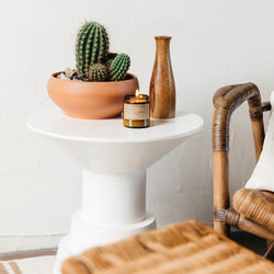 Golden Coast mini candle on a white table next to a potted cactus and wood vase with a wicker chair in front