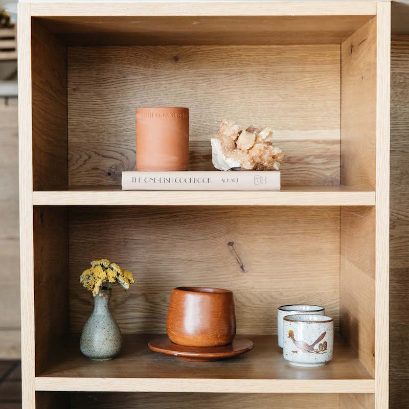 Juniper Standard terra candle on a book shelf with cups books and a vase