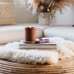 Burning lavender standard terra candle on a book on top of an ottoman with a purple crystal
