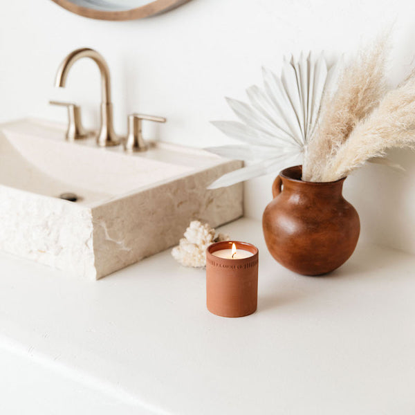 Burning night-blooming jasmine standard candle on a bathroom counter next to a sink and vase of feathers