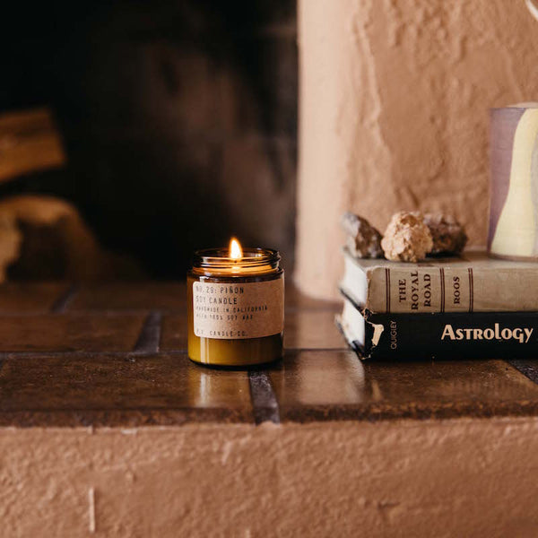 Pinon mini candle burning in front of a fire place with books to the right with a mug and rock on top