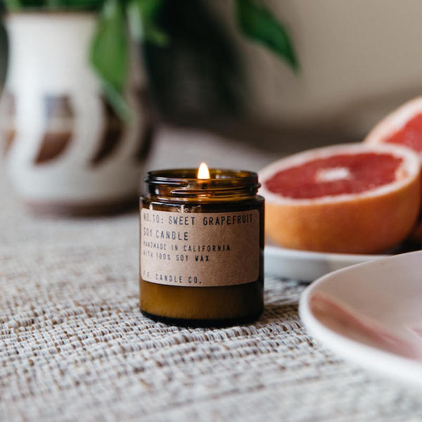 Burning Sweet Grapefruit mini candle on a tan linen table cloth next to a plate of cut grapefruit and vase of fresh flowers