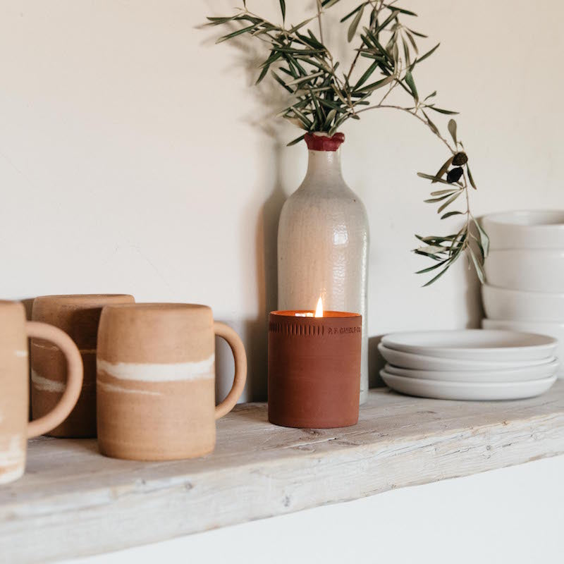 Burning western red cedar standard candle on a kitchen shelf surrounded by mugs, dishes and a vase of olive branches